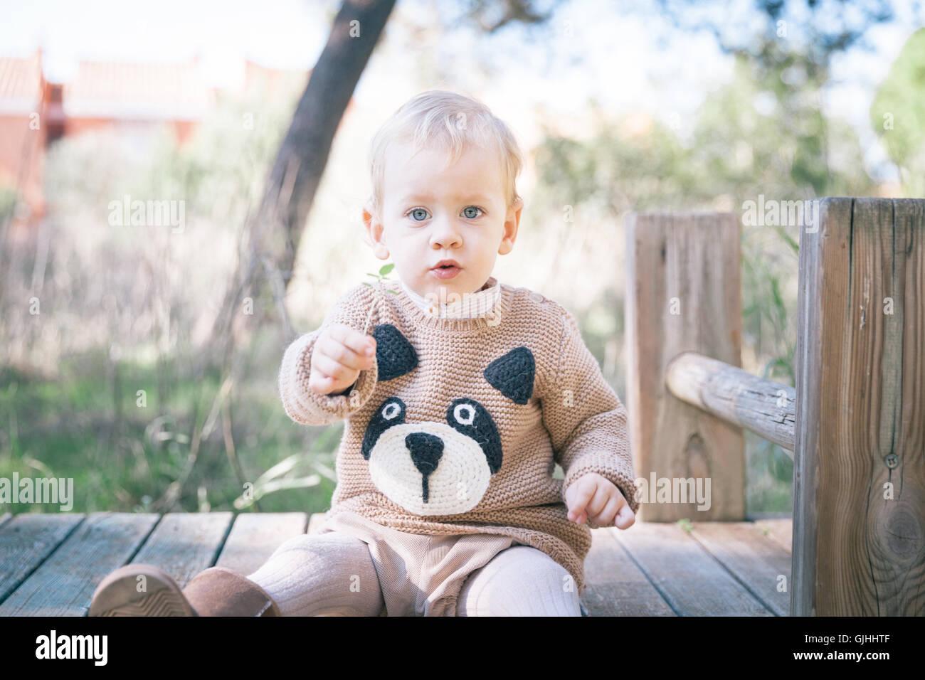 Junge sitzt auf Bauwerke in Spielplatz Stockfoto
