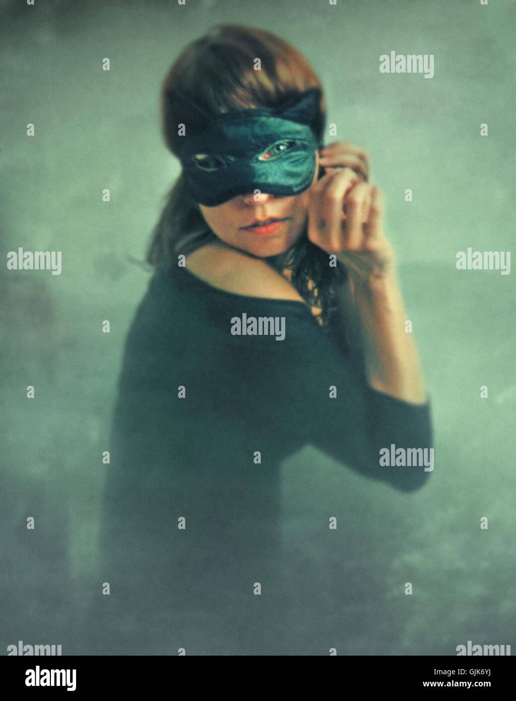 geheimnisvolle junge Frau trägt schwarze Katzenmaske im Gesicht Stockbild