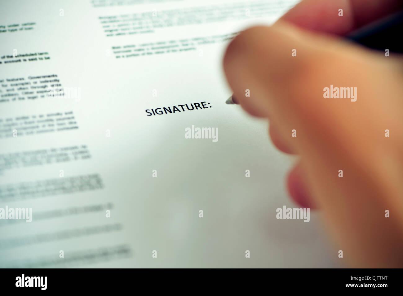 Nahaufnahme eines kaukasischen Jünglings zu signieren eines Dokuments mit einem Stift unter dem Wort Signatur Stockbild