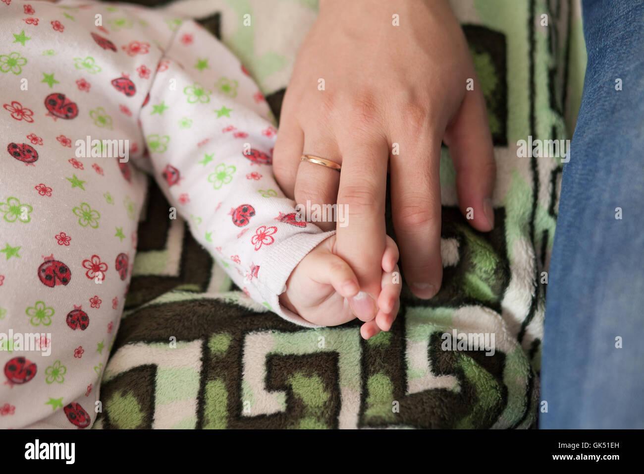 Sohn und Vater, Baby mit Papas Finger. Familienkonzept Stockfoto