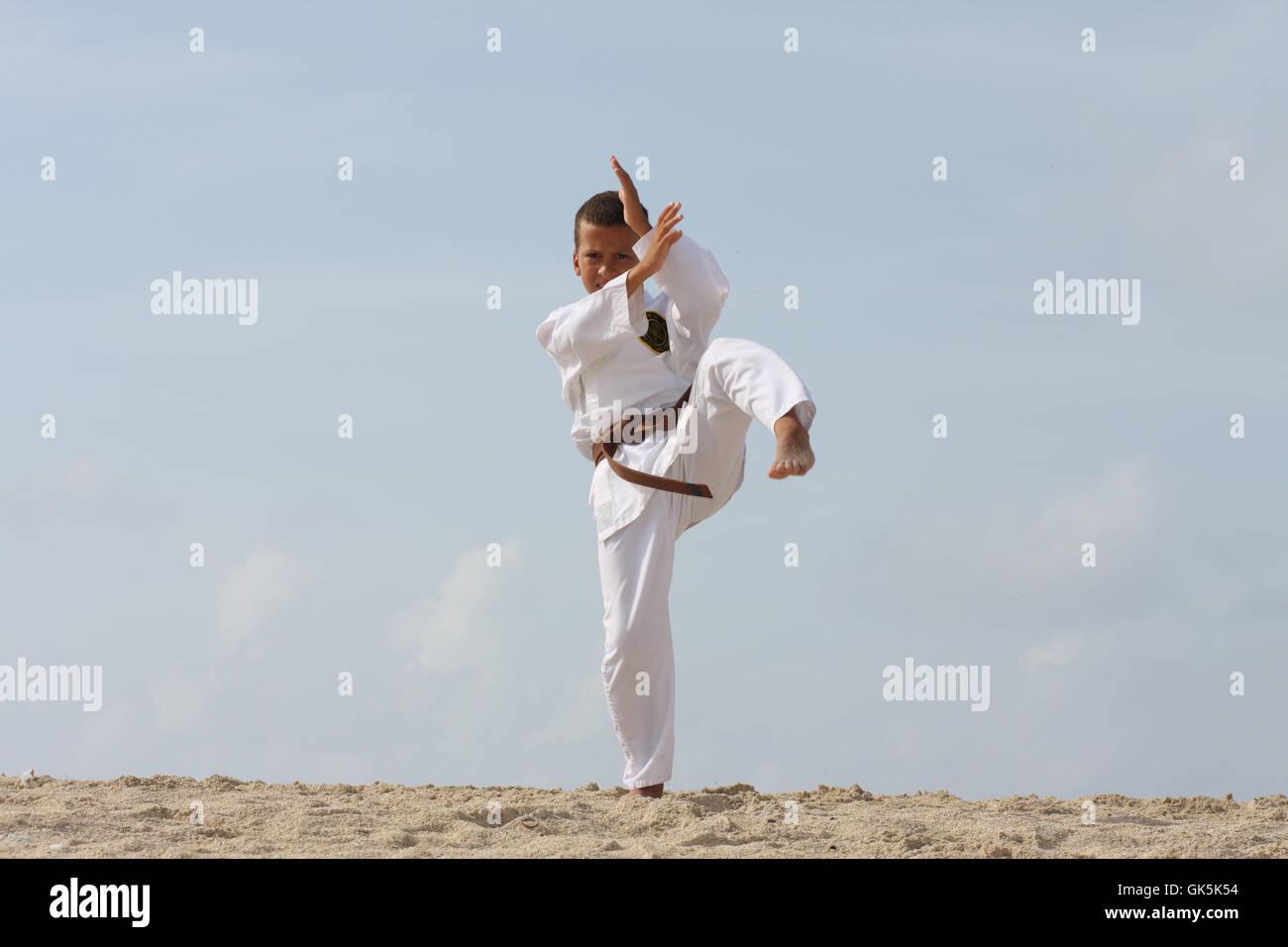 11-Jahre junge Tae Kwon Do trainieren auf der Karibik-Insel Strand zu tun. Stockbild