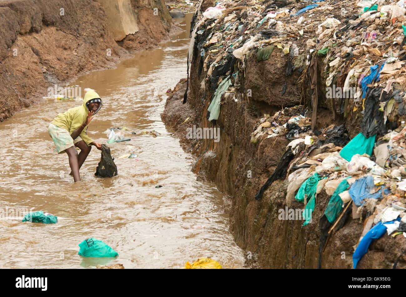 Kind spielt in üblen Fluss von Kibera Slums. Stockbild