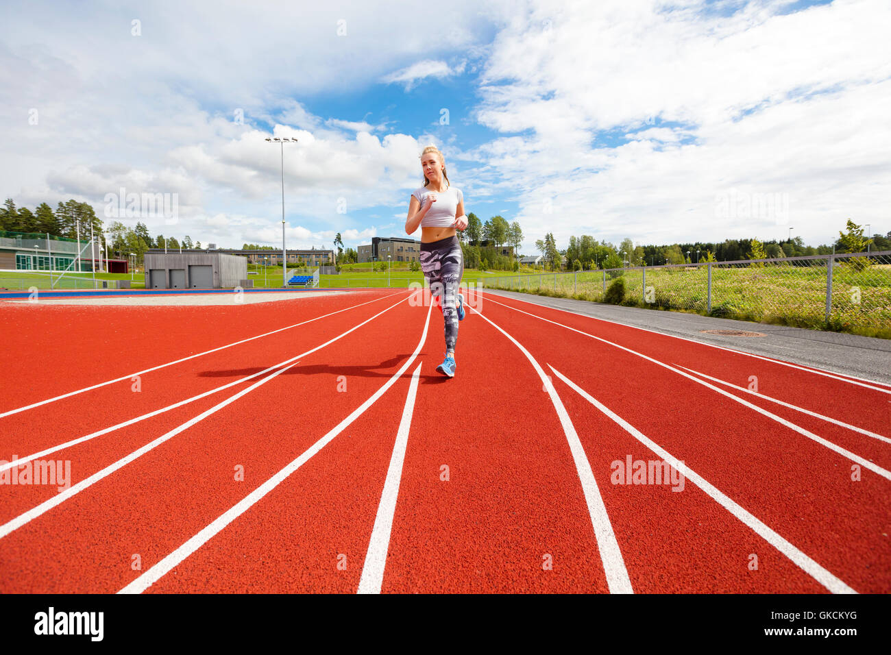 Schnelle sportliche weibliche Läufer auf Laufbahn im freien Stockbild