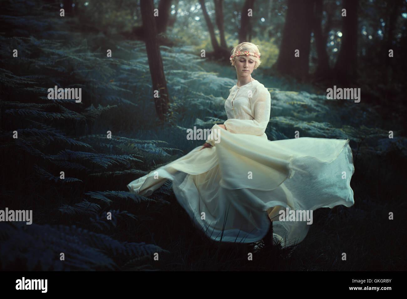 Ätherische Frau tanzt im verträumten Wald. Fantasie und surreal Stockbild