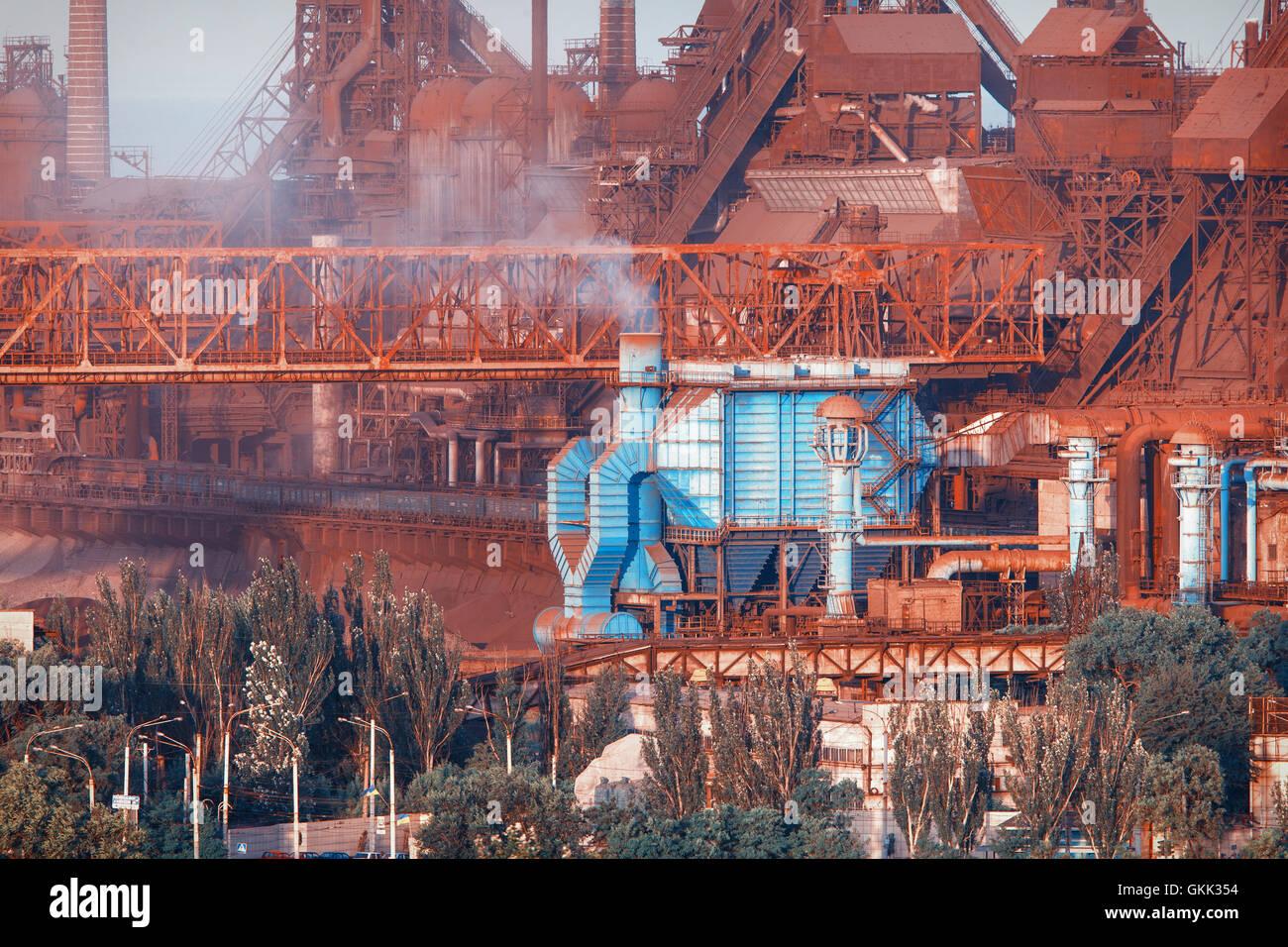 Industriebauten. Stahlwerk bei Sonnenuntergang. Rohre mit Rauch. Metallurgische Fabrik. Stahlwerke, Eisenhütte. Schwerindustrie in Stockfoto