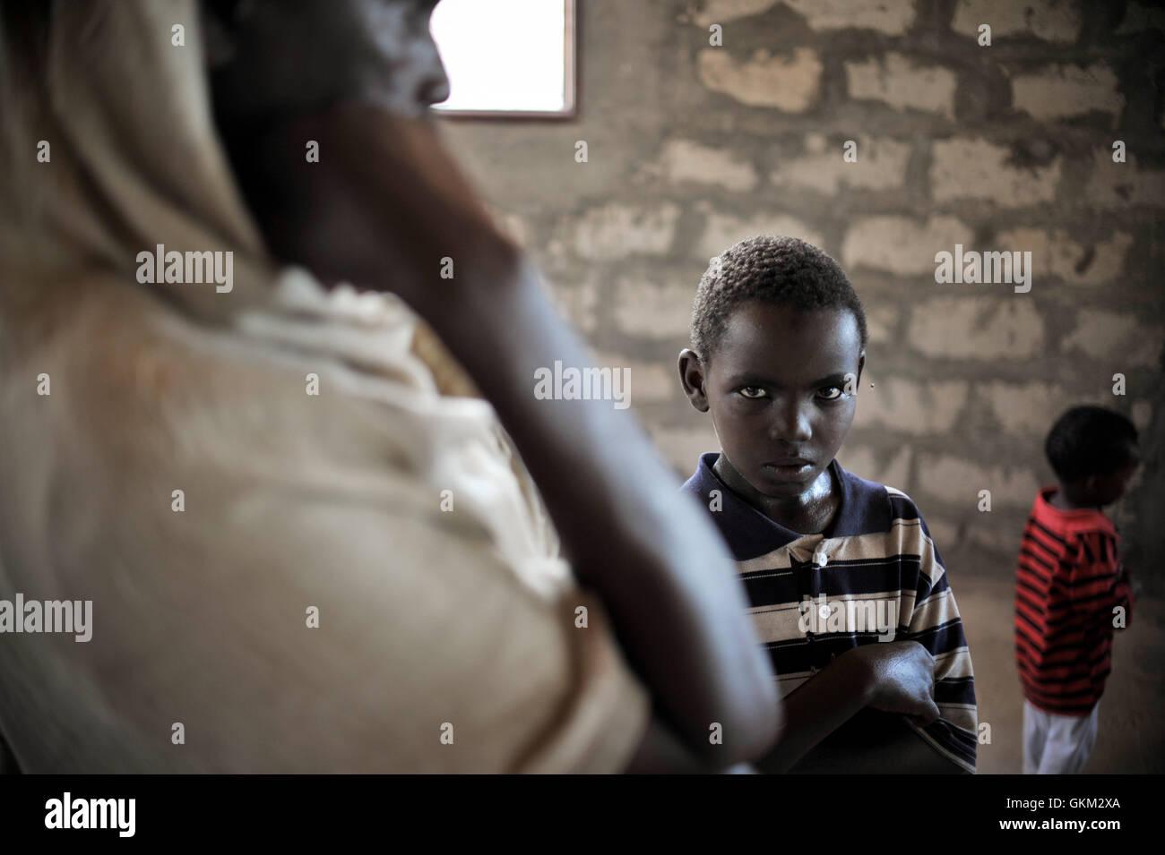 Ein Kind wartet geduldig mit seinem blinden Vater in einer medizinischen Klinik in Mogadischu, Somalia. In einer Stockbild
