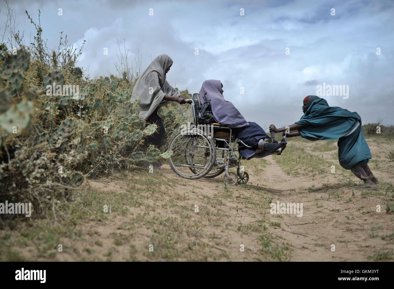 Zwei Frauen helfen anderen durch eine Hecke aus Klima bei einem Lebensmittel-Verteilzentrum in Afgoye, Somalia, Stockbild