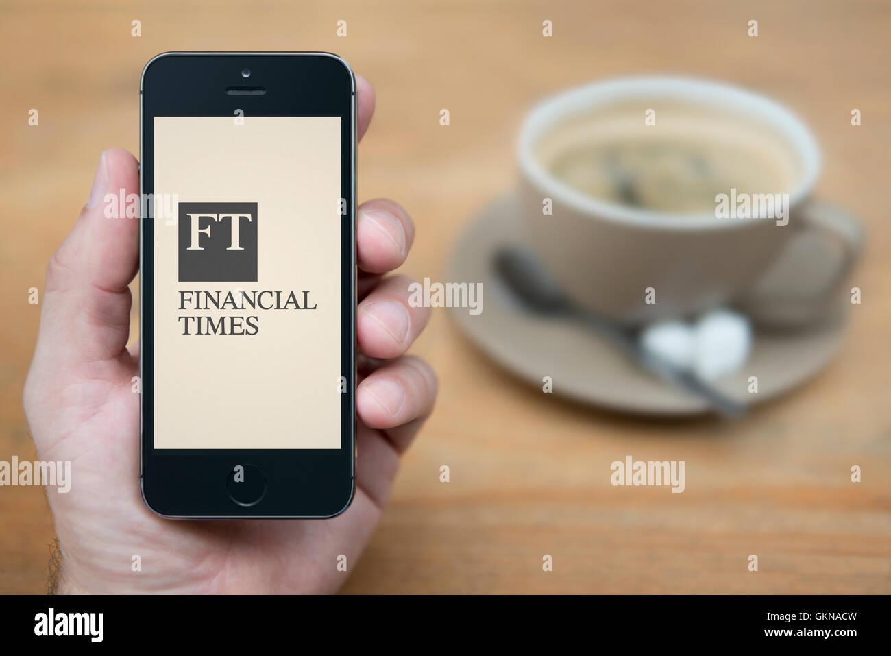 Ein Mann schaut auf seinem iPhone die Financial Times-Logo anzeigt, während mit einer Tasse Kaffee (nur zur Stockbild