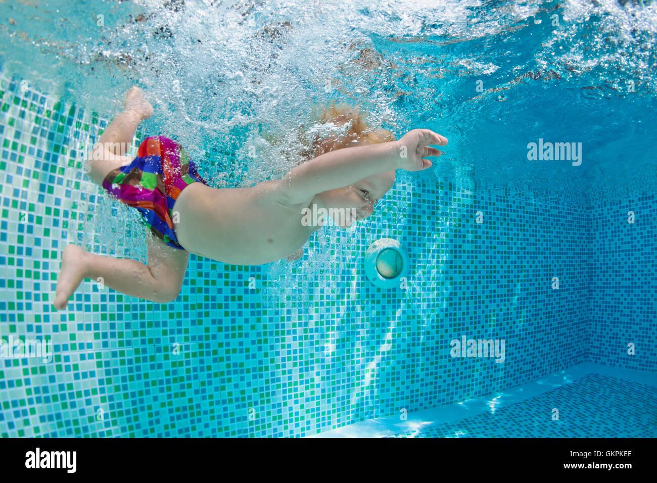 Lustiges Foto der aktiven Babyschwimmen, Tauchen im Pool mit Spaß, tief unter Wasser mit Spritzern und Schaum Stockbild