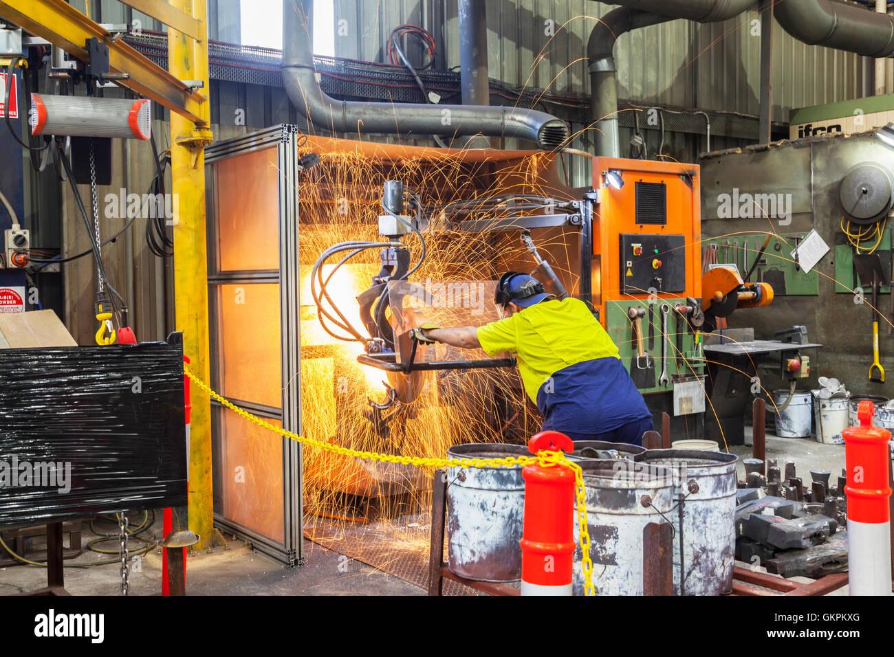 """Arbeiter, Schleifen oder Schneiden entfernt werfen Metallkomponenten aus seinem """"Casting"""" Baum. Stockfoto"""