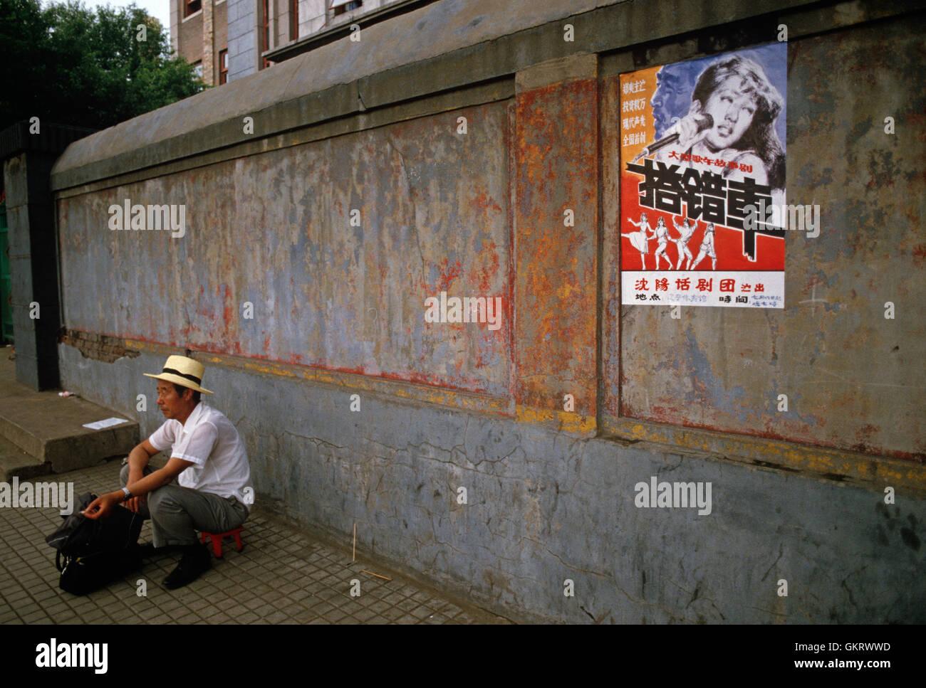 Mann kauert sich neben Wand mit Popmusik Poster, Shenyang, China. Stockfoto