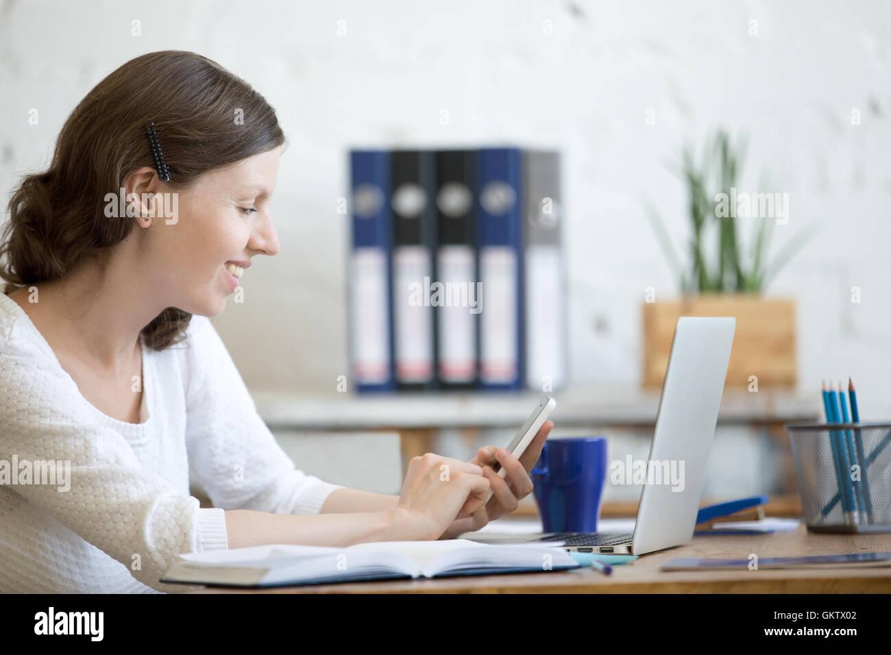Porträt der glückliche junge Geschäftsfrau arbeiten im home-Office Interieur im Loft holding Smartphone Stockbild