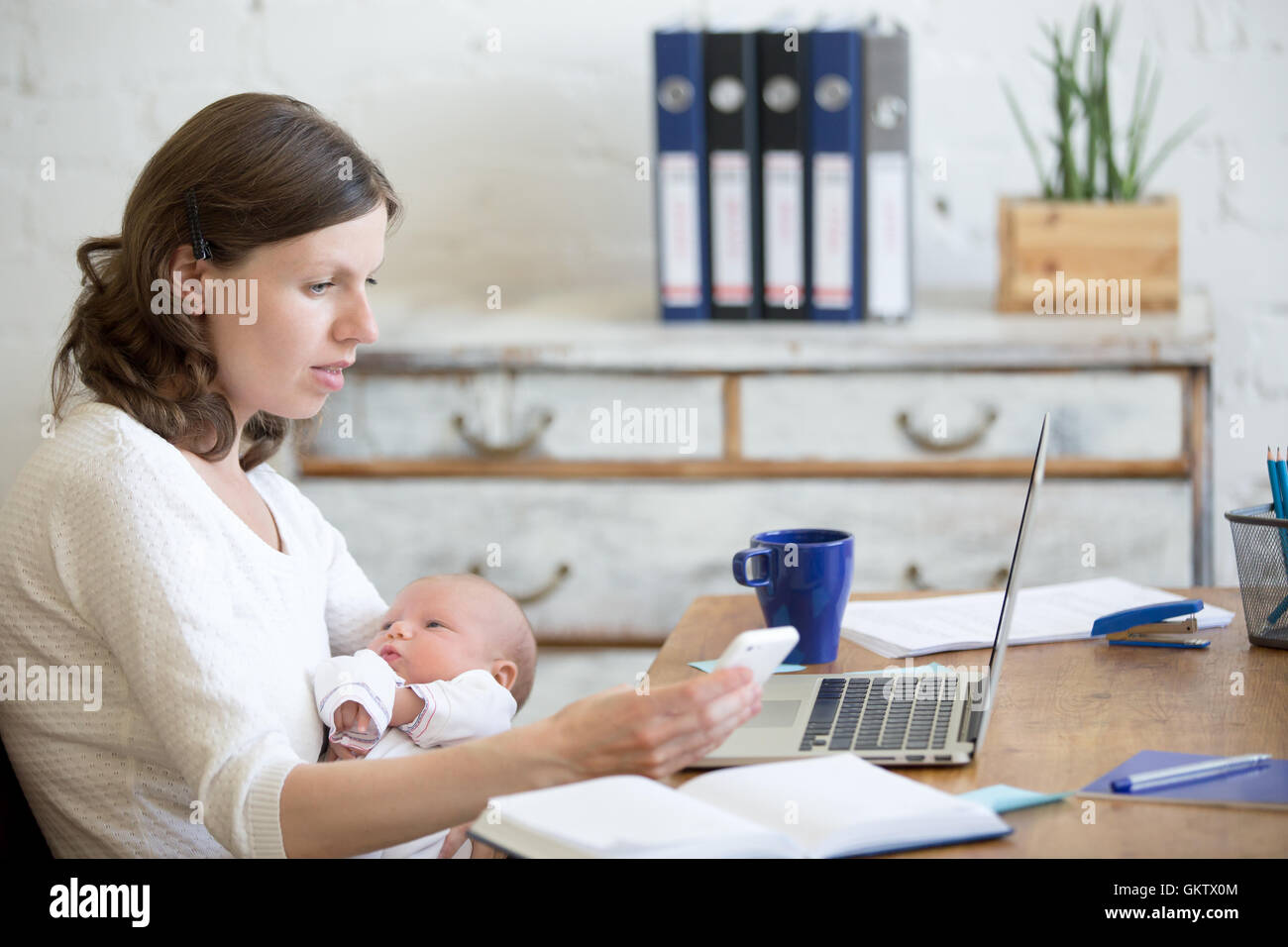 Porträt von Jungunternehmen Mutter hält ihr Neugeborenes niedliches Baby beim Arbeiten im home-Office Stockbild