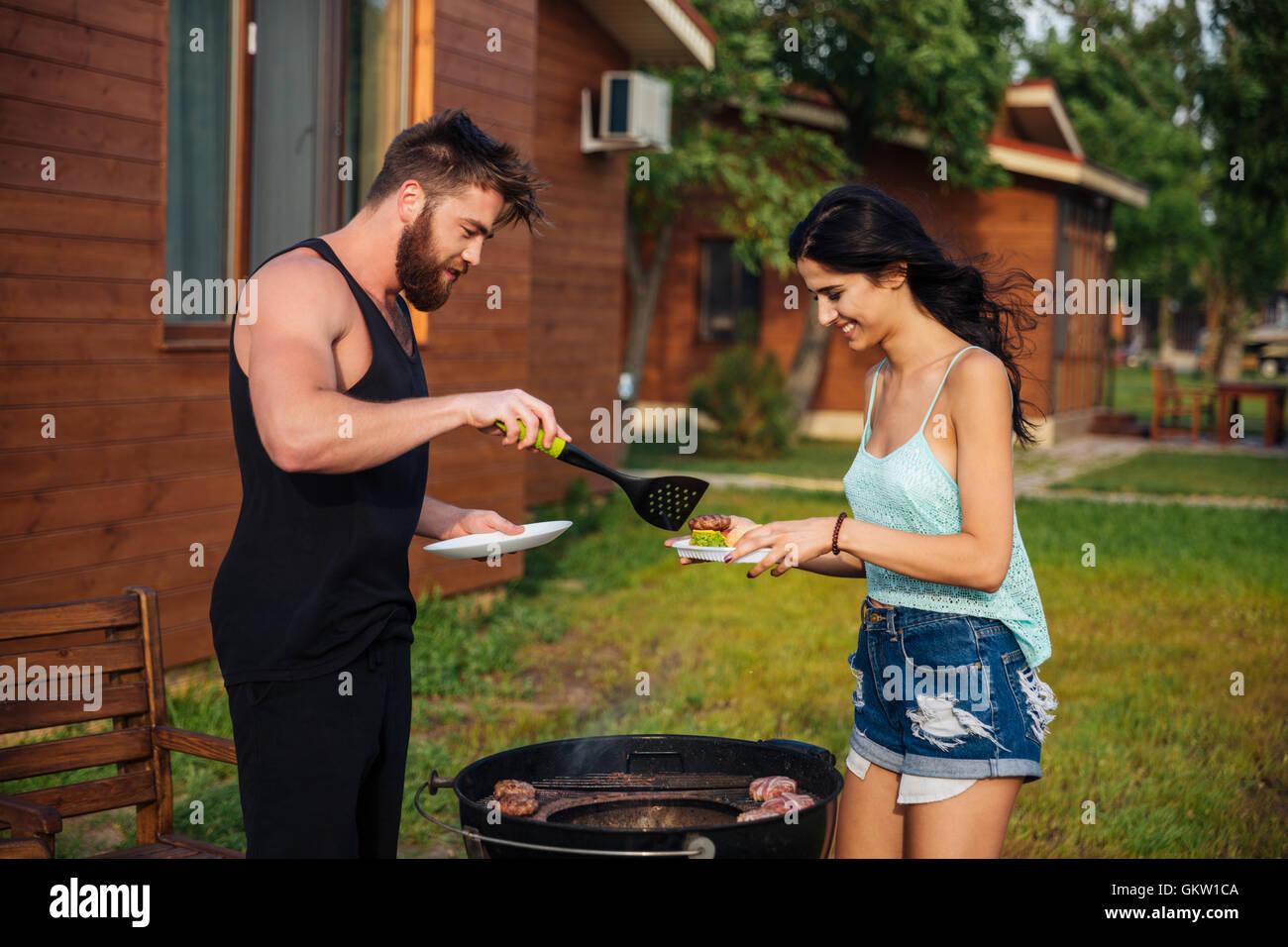Glückliches junges Paar stehen und Kochen treffen auf Barbecue-Grill im freien Stockbild