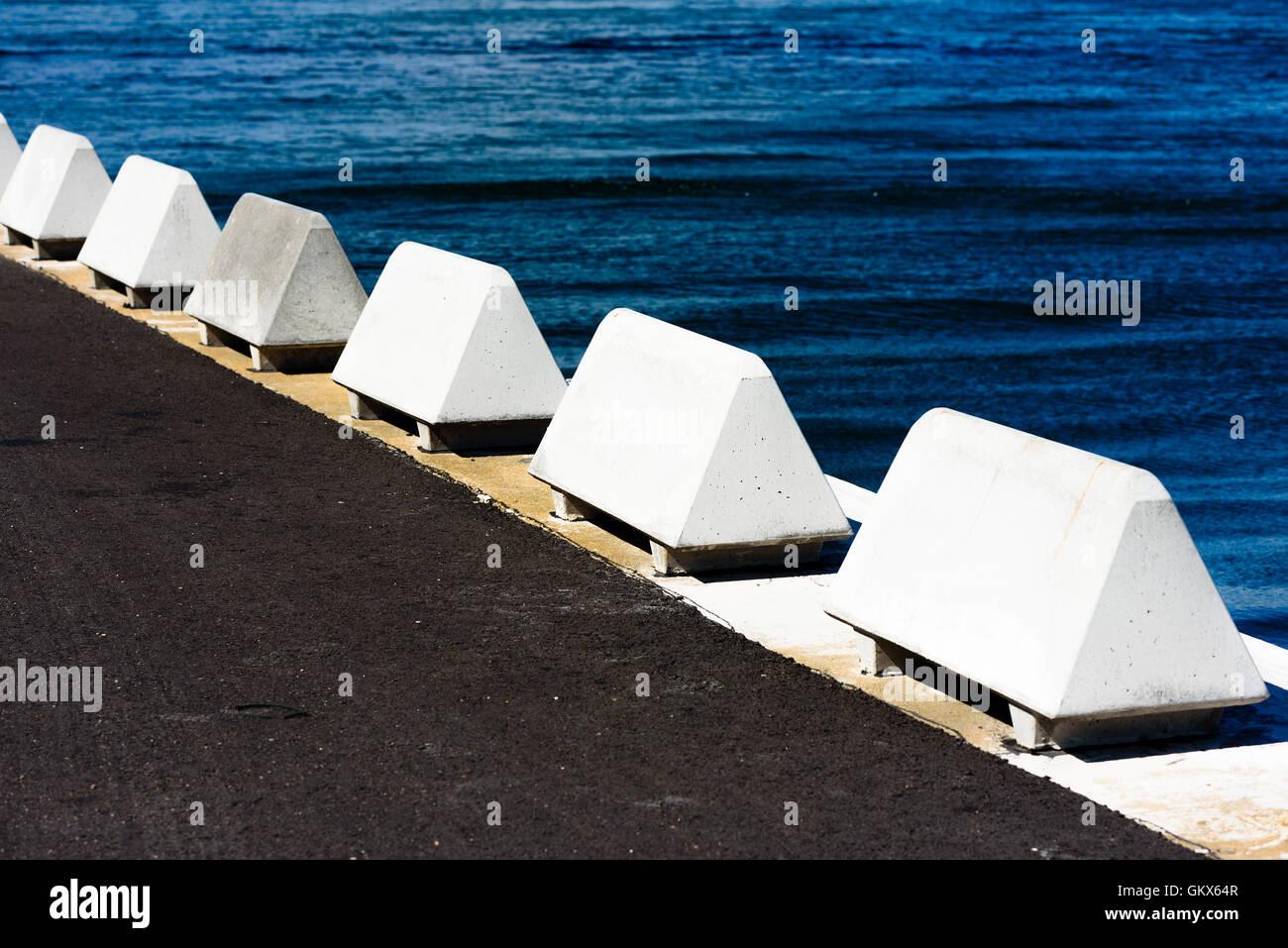 Dreieckige Betonsteinen stehen in einer Reihe entlang am Hafen zu verhindern, dass Datenverkehr der Kante fahren. Stockbild
