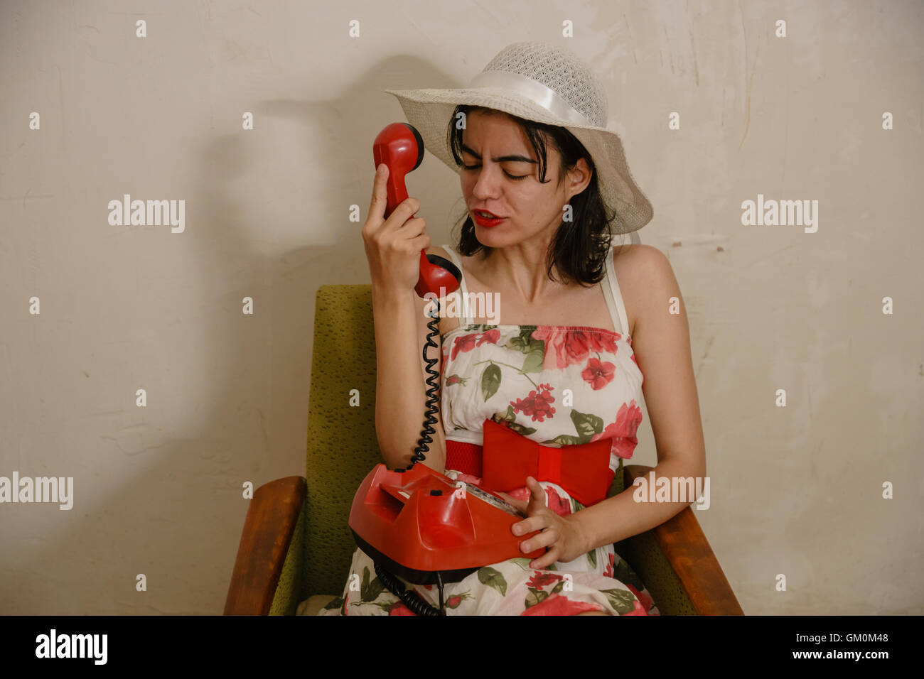 hübsche Brünette spricht emotional per Telefon auf den alten Lehnstuhl sitzen Stockbild