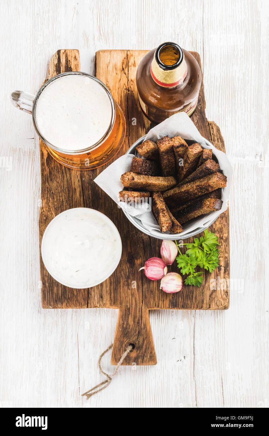 Bier-Snack-Set. Pint Pilsener im Becher, offene Glasflasche, Schwarzbrot-Croûtons mit Knoblauch Frischkäse Stockbild