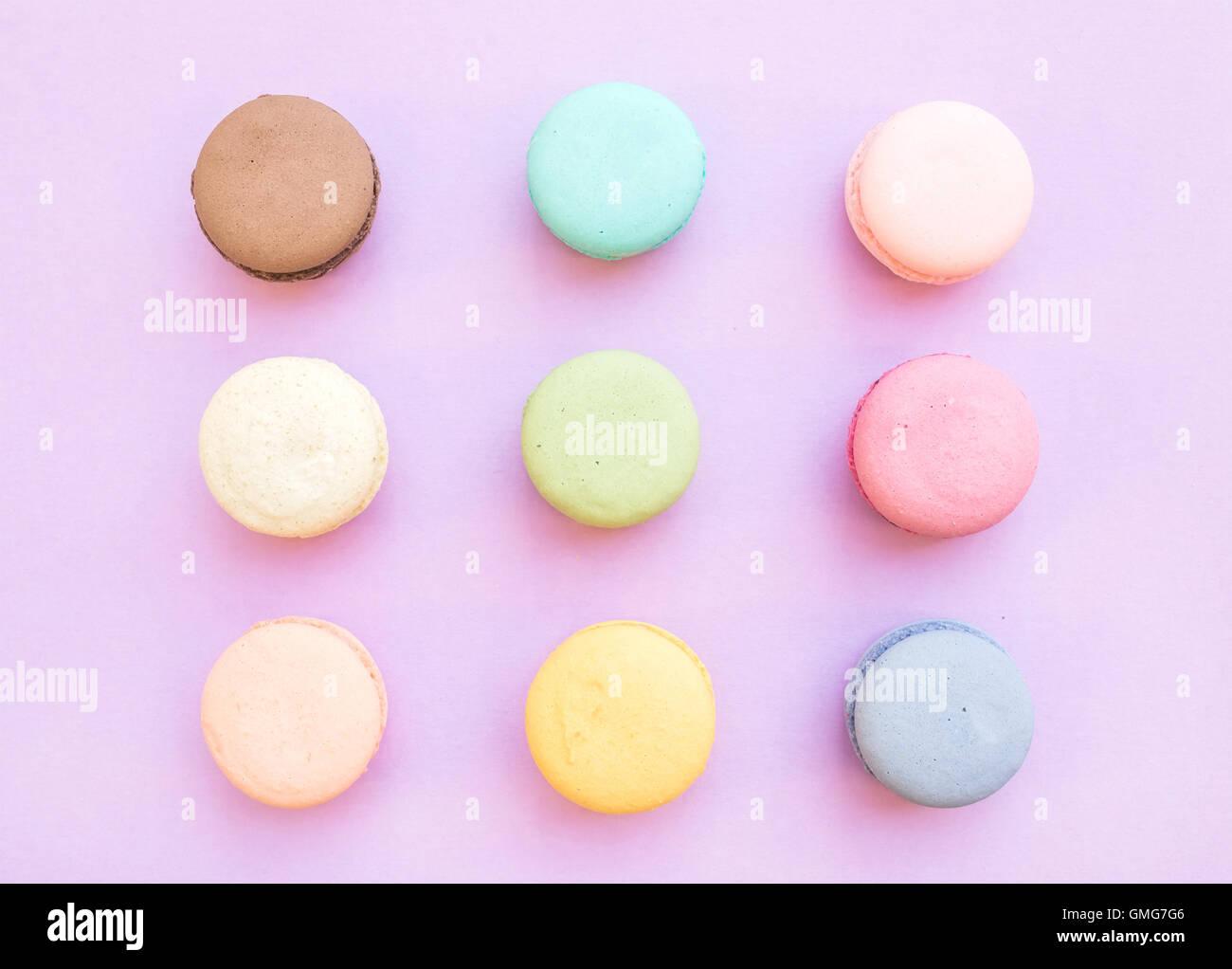 Süße bunte französische Makronen Kekse auf Pastell lila Hintergrund Stockbild