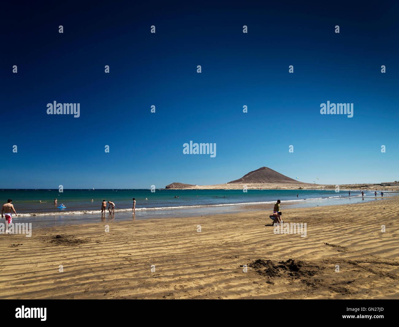 Toursists in el Medano Strand und Montana Roja Berg Wahrzeichen im Süden von Teneriffa Insel Spanien Stockbild