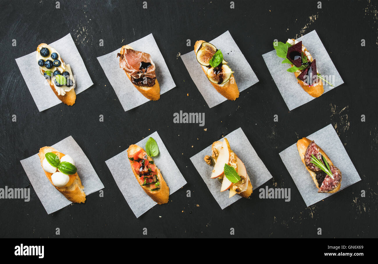 Italienische Crostini mit verschiedenen Toppings auf Backpapier weiß Stockbild
