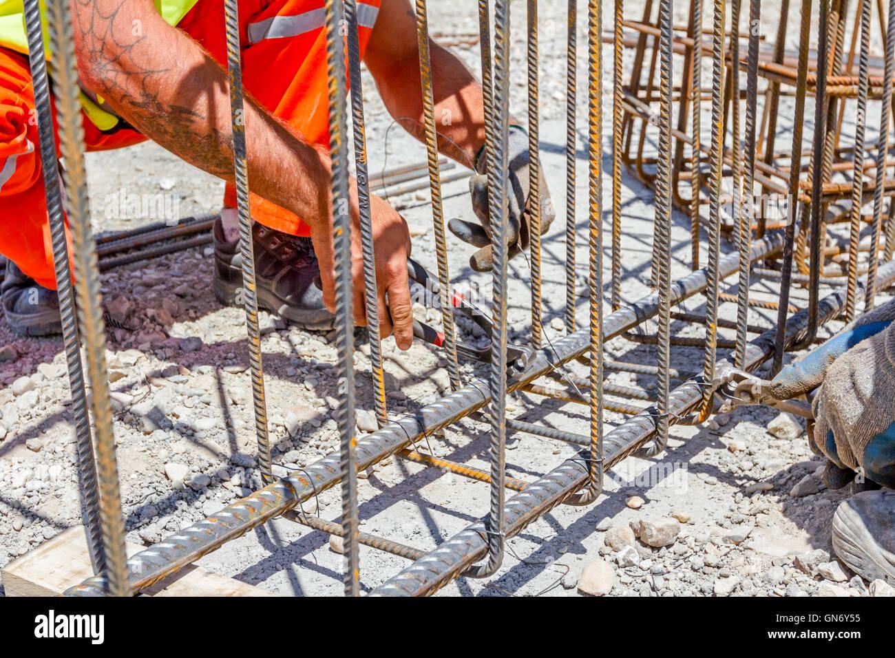 Arbeitnehmer sind Bewehrung um einen neu errichteten Fundament ...