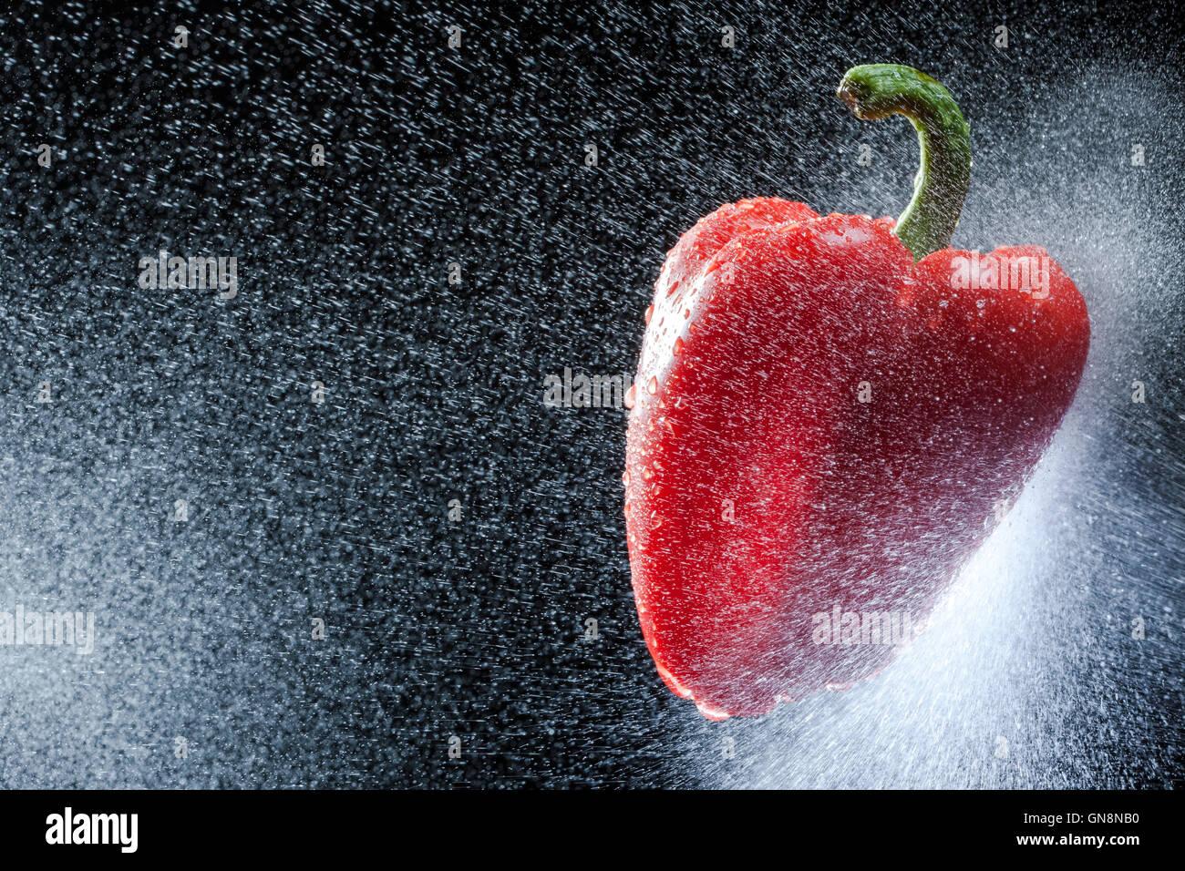 Rote Paprika in einem Spray gegen einen schwarzen Hintergrund. Eine Reihe von Obst und Gemüse in Bewegung. Stockbild