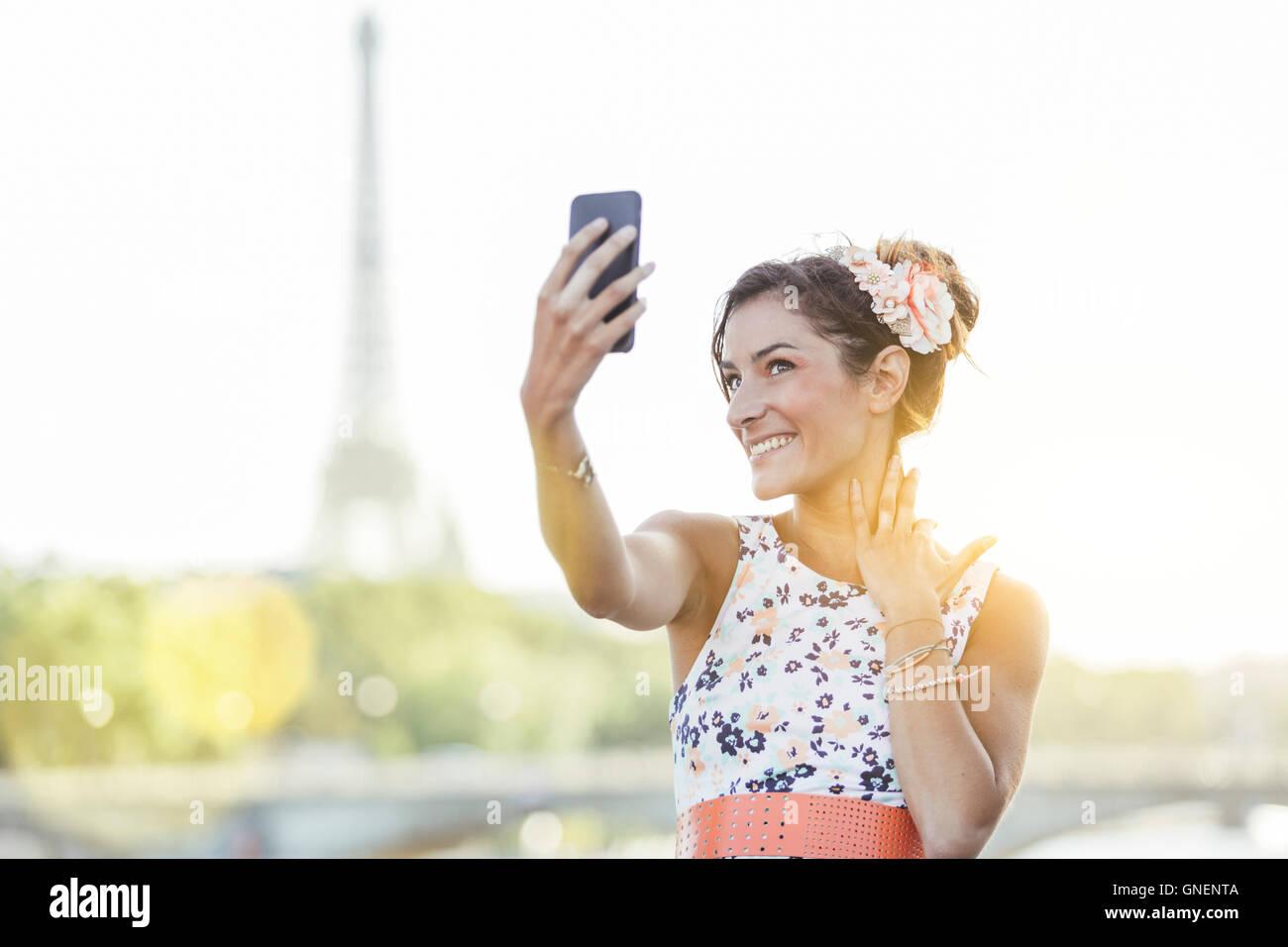 Paris, Frau tut ein Selbstporträt mit Eiffelturm im Hintergrund Stockbild