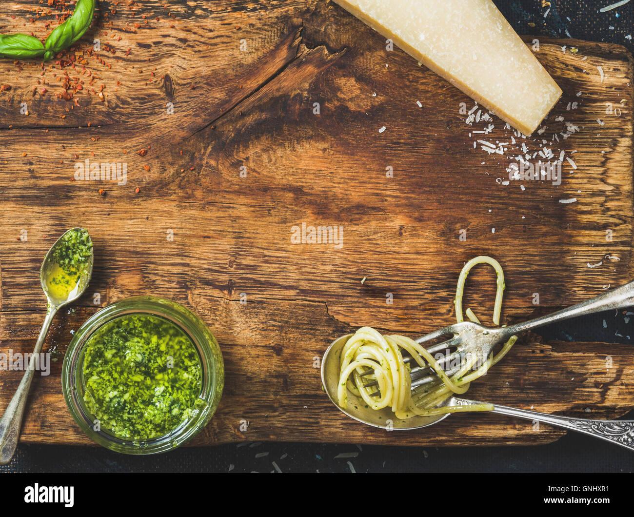 Italienische Küche kochen Hintergrund. Glas mit Pesto-Sauce, Löffel und Gabel mit gekochten Spaghetti, Stockbild