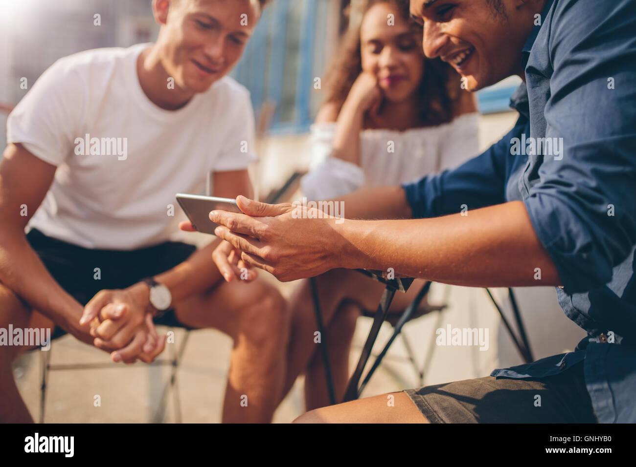Junge Leute sitzen im Freien und Blick auf Handy. Gruppe von Freunden im Café im Freien sitzen und Viedeo auf Stockbild