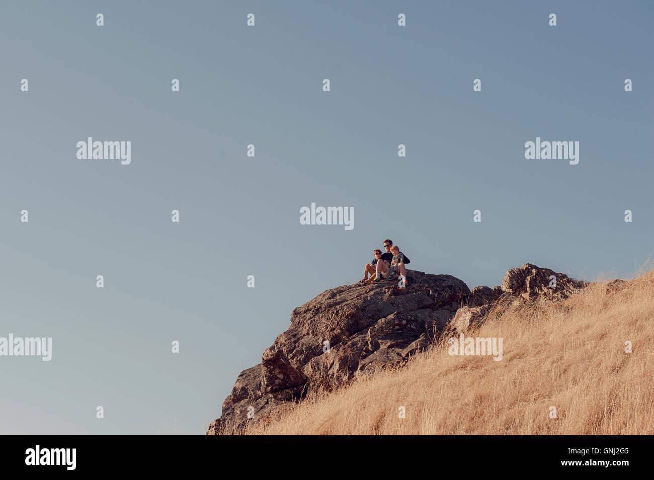 Vater und zwei Söhne auf Felsen sitzend, Mount Tamalpais, Kalifornien, Vereinigte Staaten Stockfoto