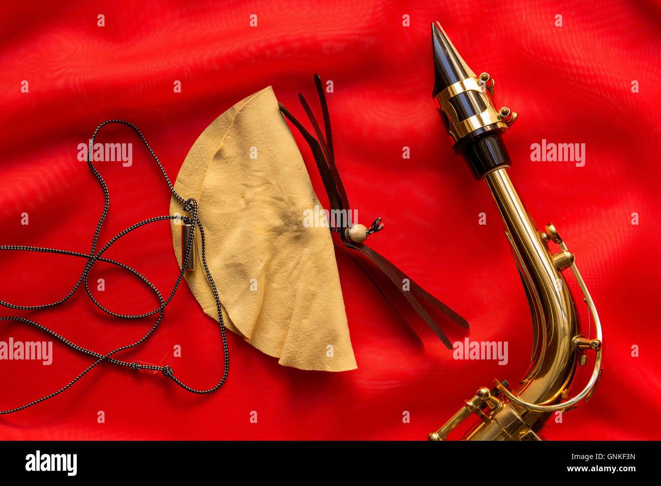 Wildleder Bürste und Saxophon Mundstück auf rotem Grund Stockbild