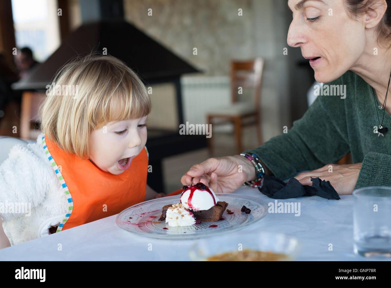 zwei Jahre überrascht Kind mit orangefarbenen Lätzchen lustig Essen mit Frau ein Stück Schokoladenkuchen Stockbild