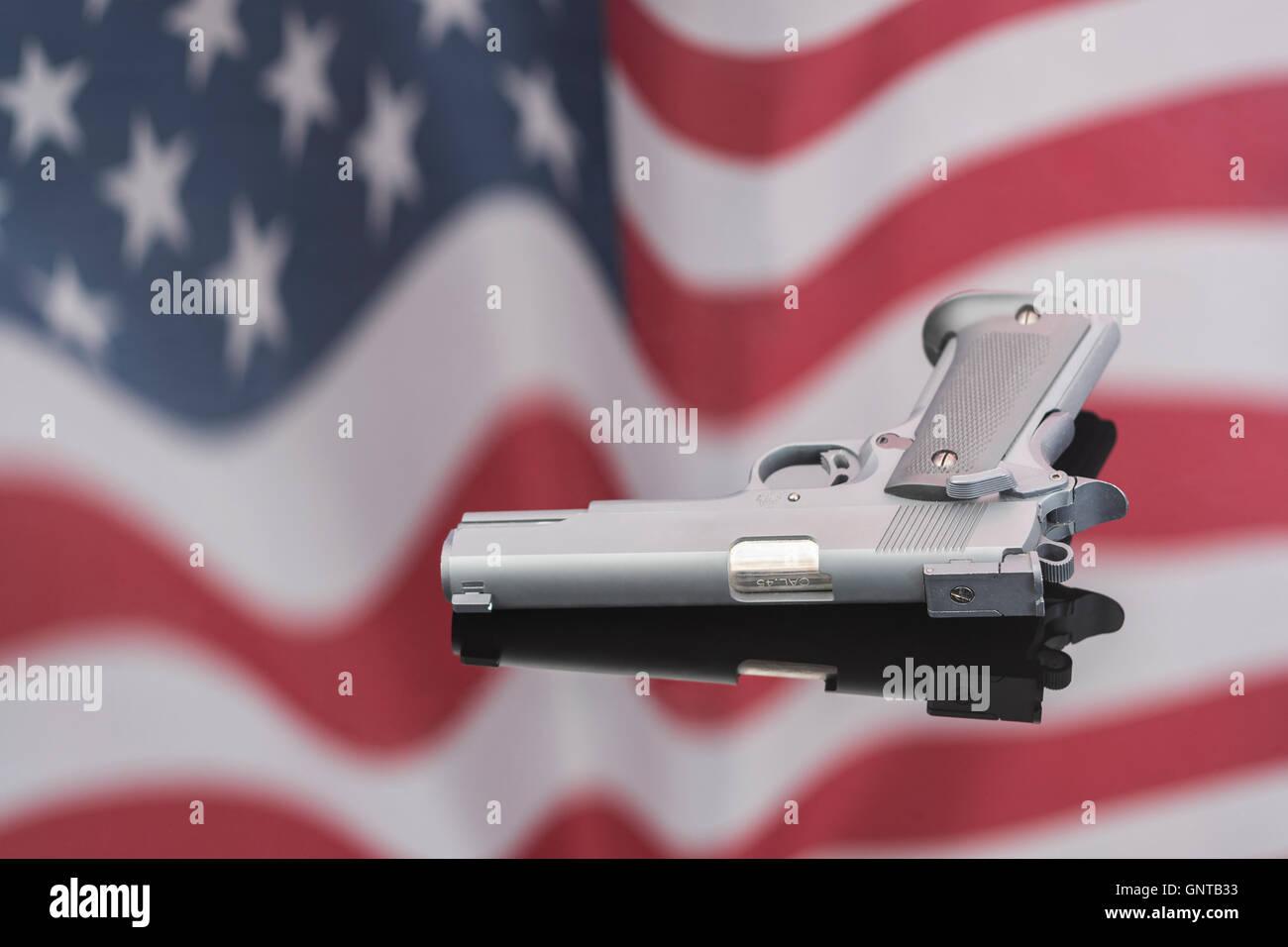 Replika Colt 1911 a gegen Reflexion der US Flag/Stars & Stripes - visuelle Metapher für Waffenbesitz, US Stockbild