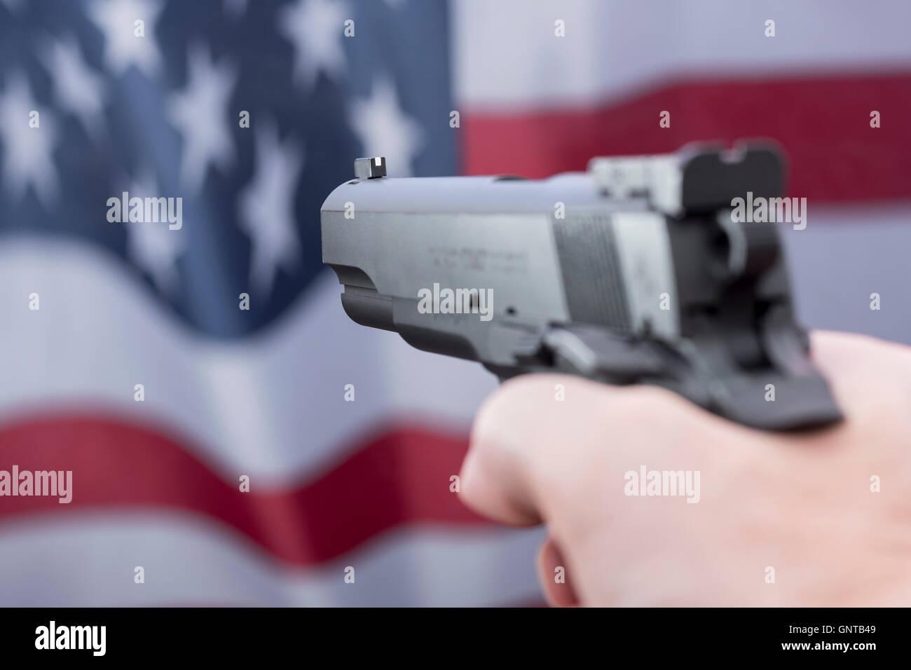 Replika Colt 1911 ein Satz gegen Reflexion der US Flag/Stars & Stripes - als Metapher für die Gun Control, Stockbild