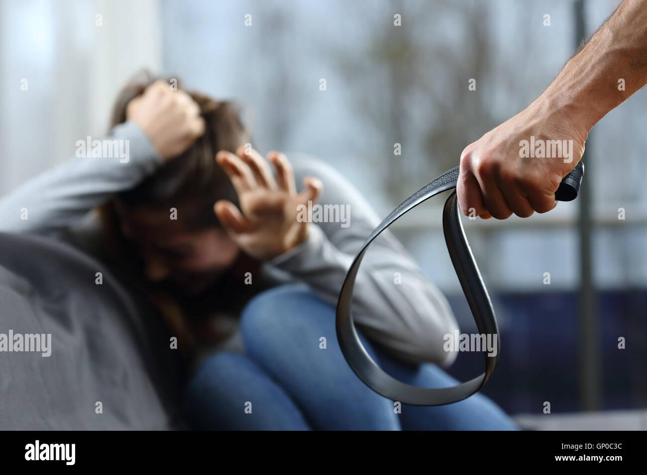 Angst vor Frau droht mit einem Gürtel von ihrem Ehemann zu Hause mit einem Fenster im Hintergrund an einem Stockbild