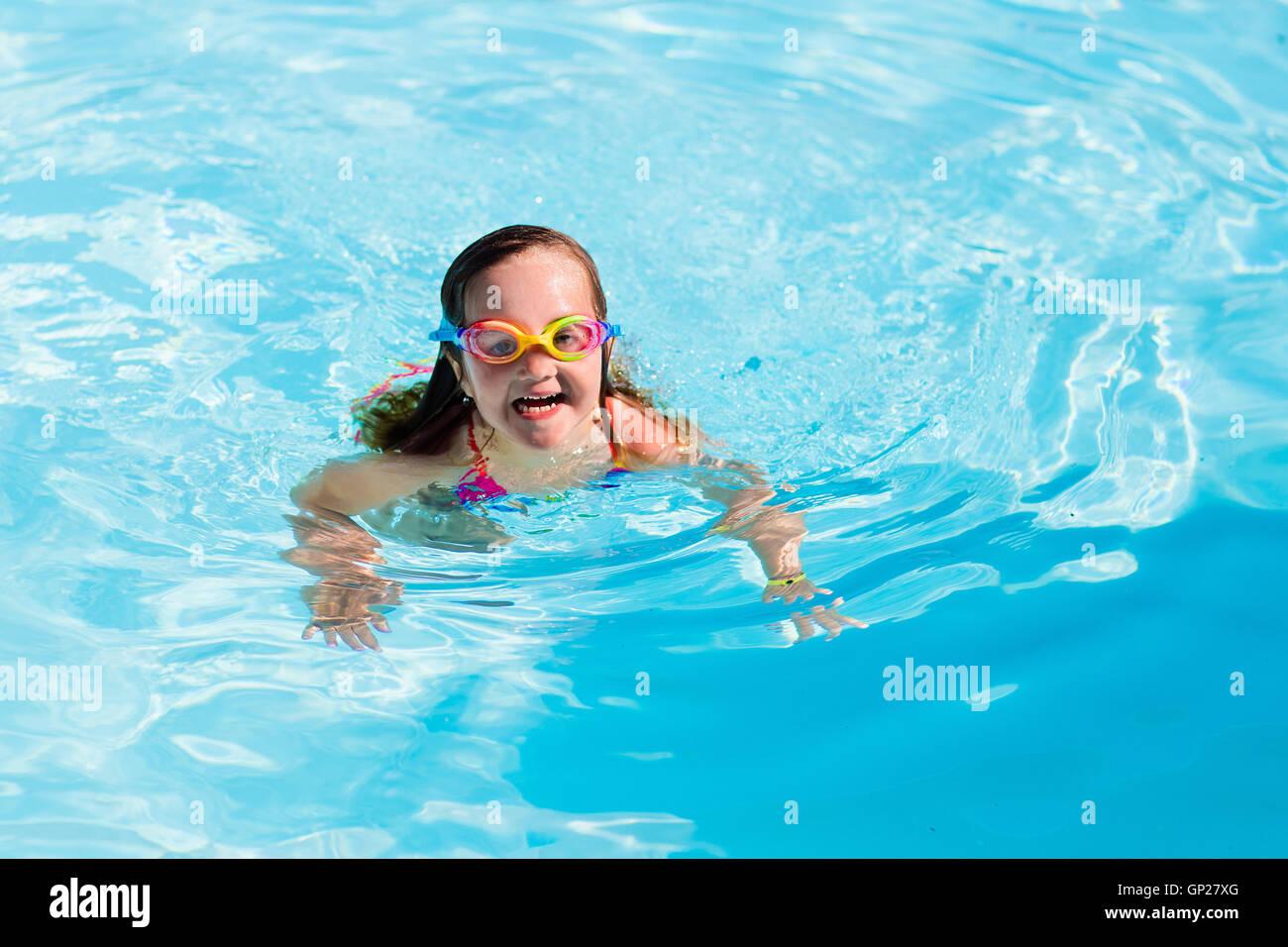 10c6e2a25c219 Glückliche kleine Mädchen lernen zu schwimmen und Tauchen im Schwimmbad im  Freien an heißen Sommertag in tropischen Resort. Kind trägt Brille