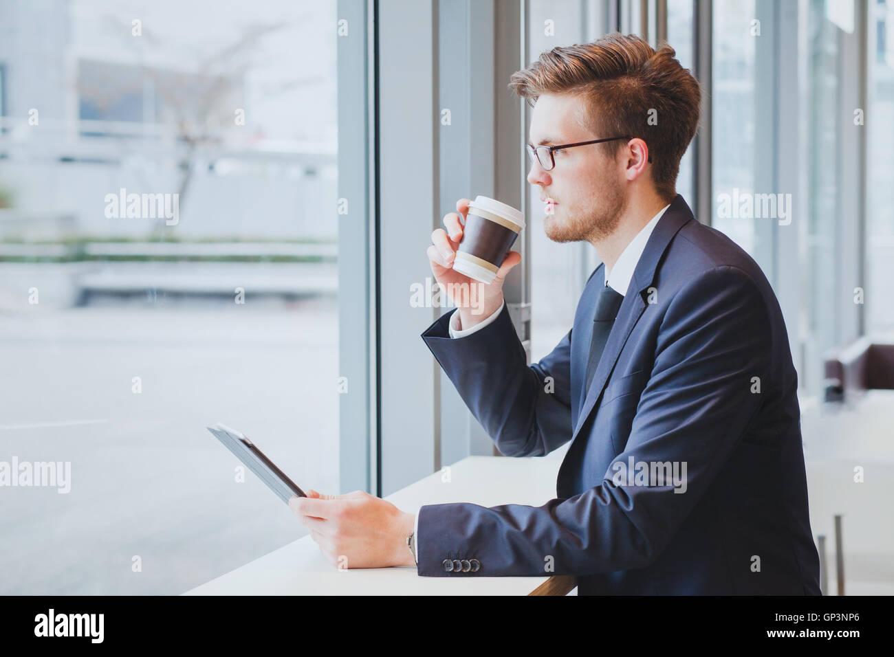 Business-Mann denken, Kaffee trinken und mit Blick auf das Fenster im modernen Café-Interieur Stockbild