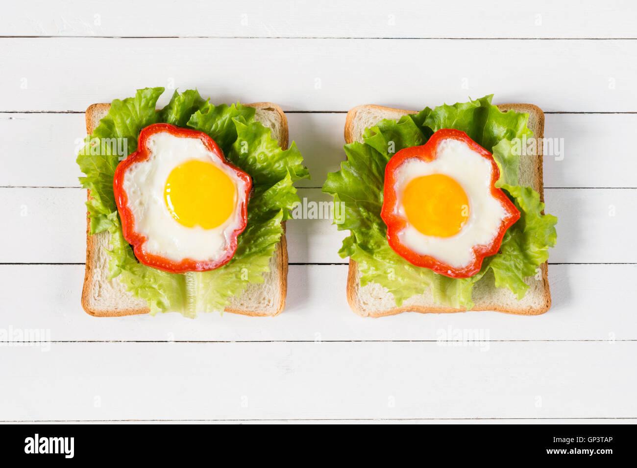 Frühstücks-Sandwich mit Ei, Käse und grünem Salat. Draufsicht auf gesunde Ernährung. Kreative Stockbild