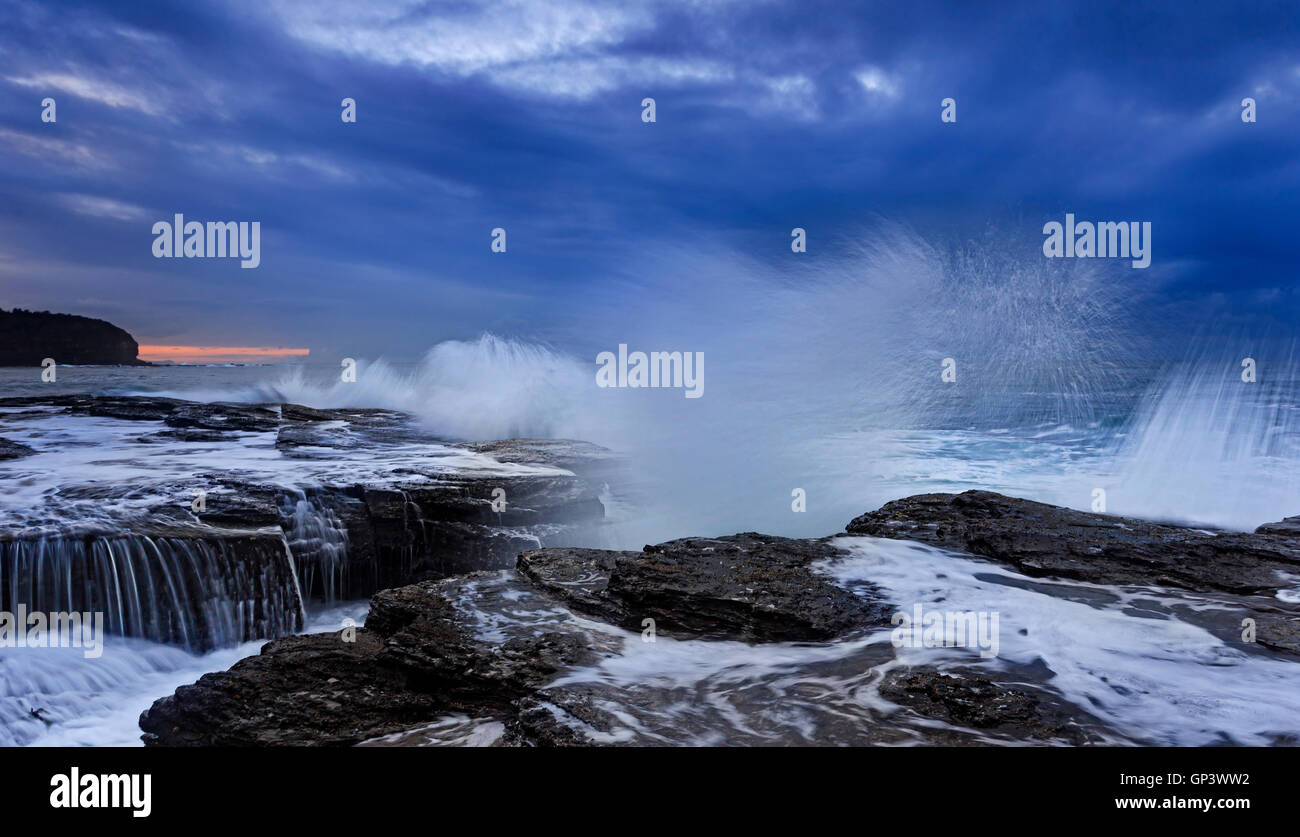 Starke Spritzer nähert sich Ozeanwelle erodieren Sandsteinfelsen von Australien Pazifik Küste in der Nähe Stockbild