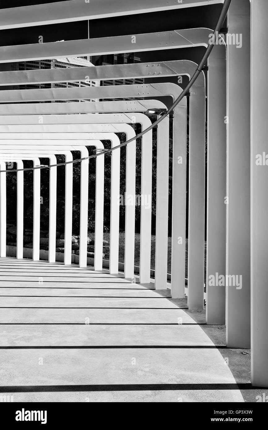 vertikale Perspektive abstrakte Galerie umrahmt von Spalten durch Sonnenlicht im schwarz-weiß-Format zu vergießen. Stockbild