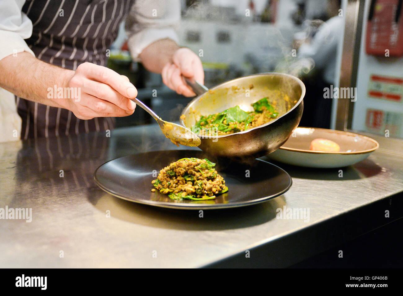 Restaurant-Chef platzieren gekocht Linsengericht auf Platte Stockbild
