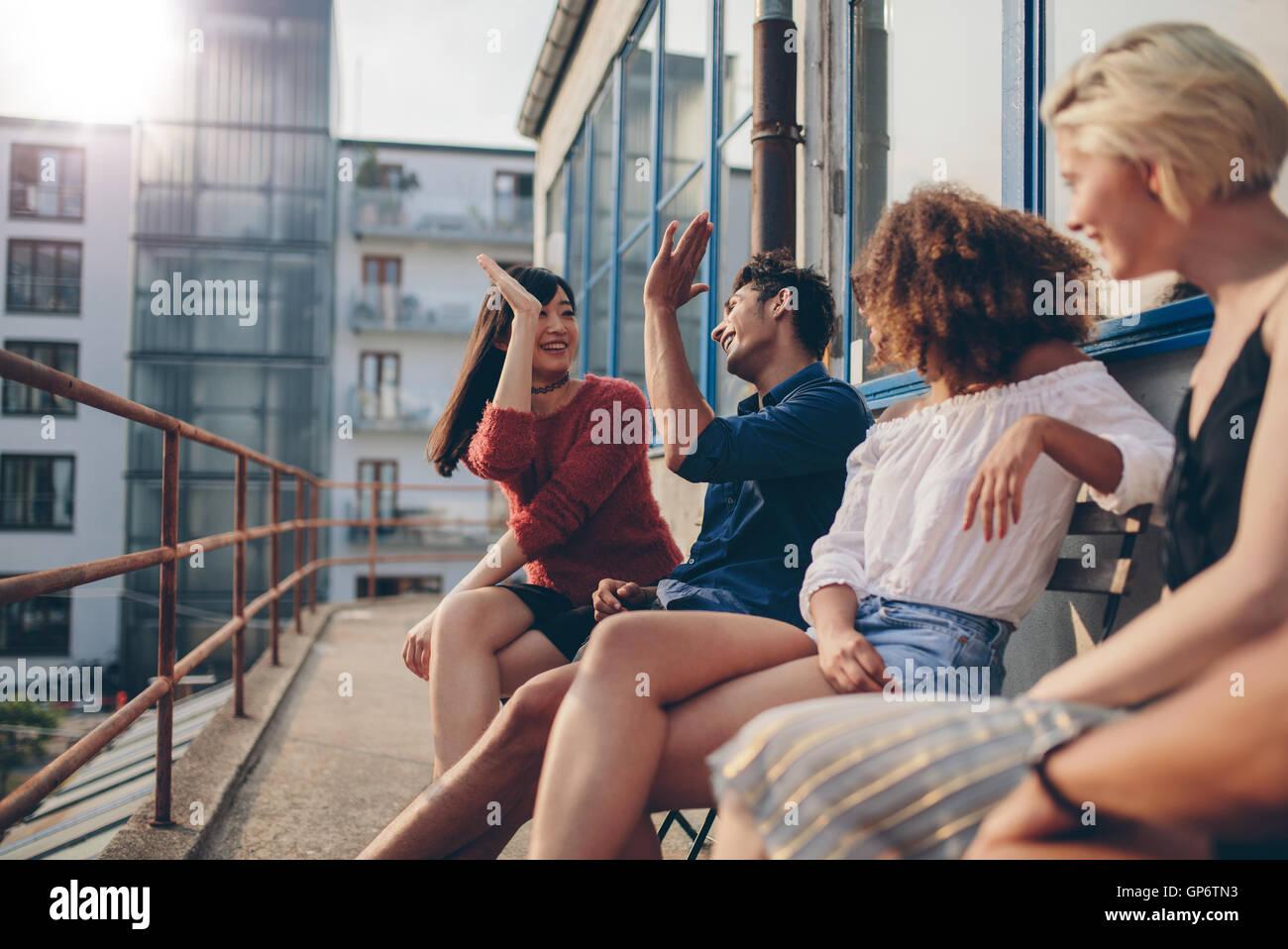 Gemischtrassigen Gruppe von Freunden Spaß in Balkon und geben hohe fünf. Junge Leute auf der Terrasse genießen. Stockfoto