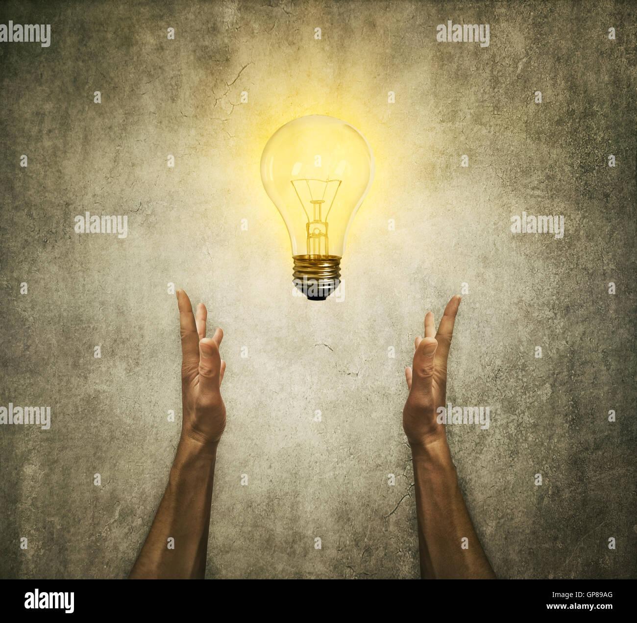 Nahaufnahme von zwei menschliche Hände halten eine Glühbirne. Kreativität und Idee Konzept Stockbild