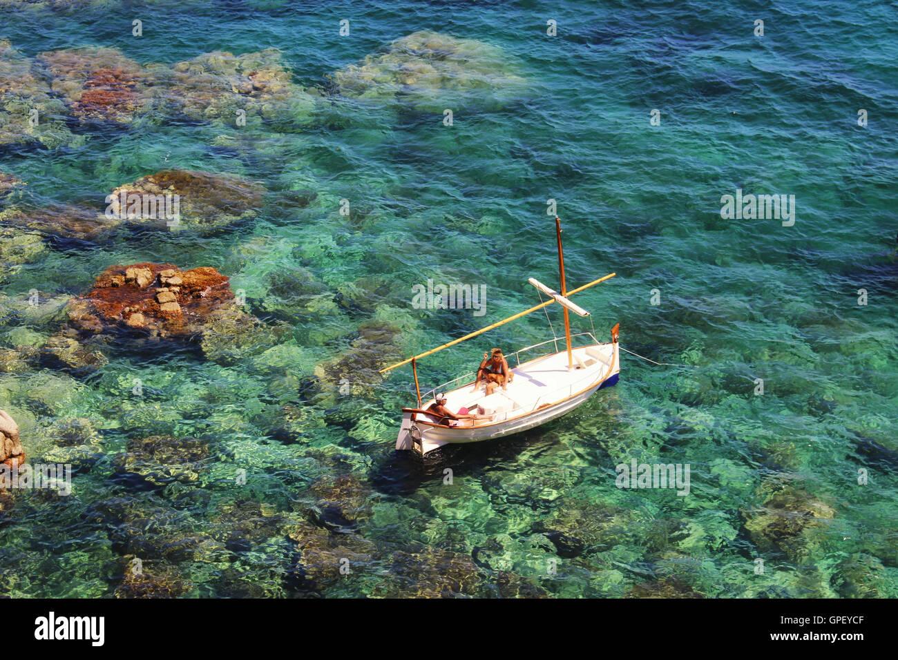 Girona, Spanien - 14. August 2016: Menschen, die die Sonne auf einem Boot über das transparent grüne Mittelmeer Stockbild