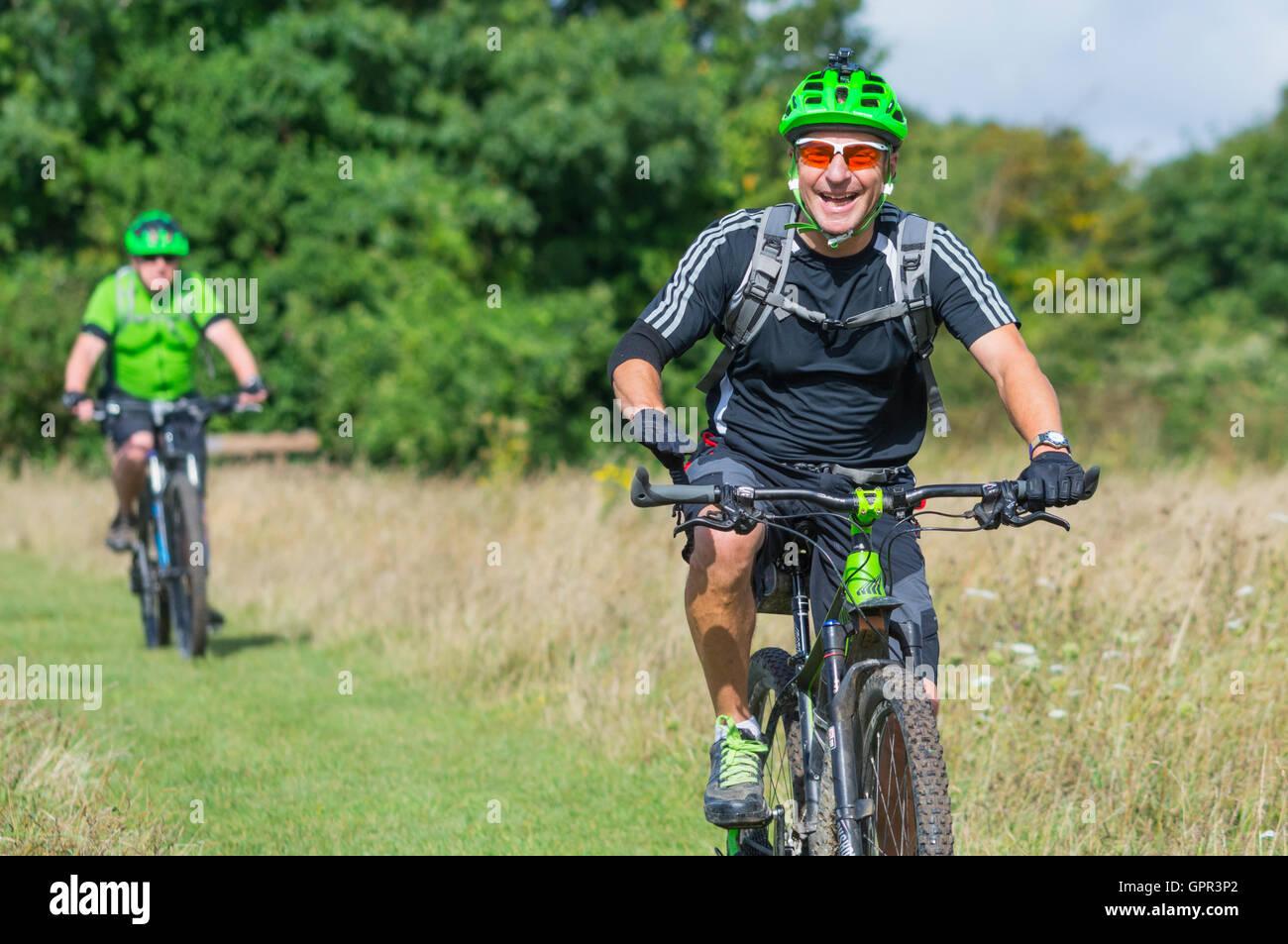 Radfahrer mit Helmen auf dem Lande genießen die Fahrt auf den South Downs in West Sussex, England, UK. Stockbild
