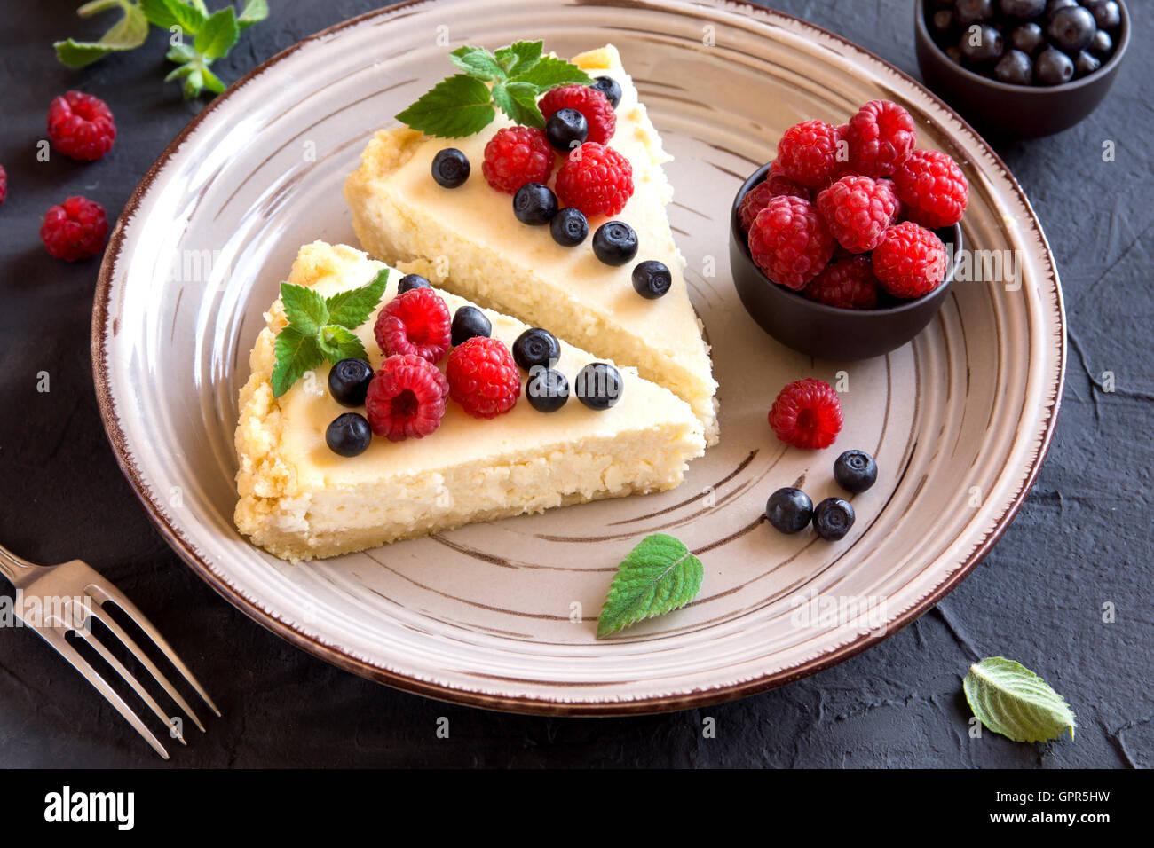 Hausgemachter Käsekuchen mit frischen Beeren und Minze zum Nachtisch Stockbild
