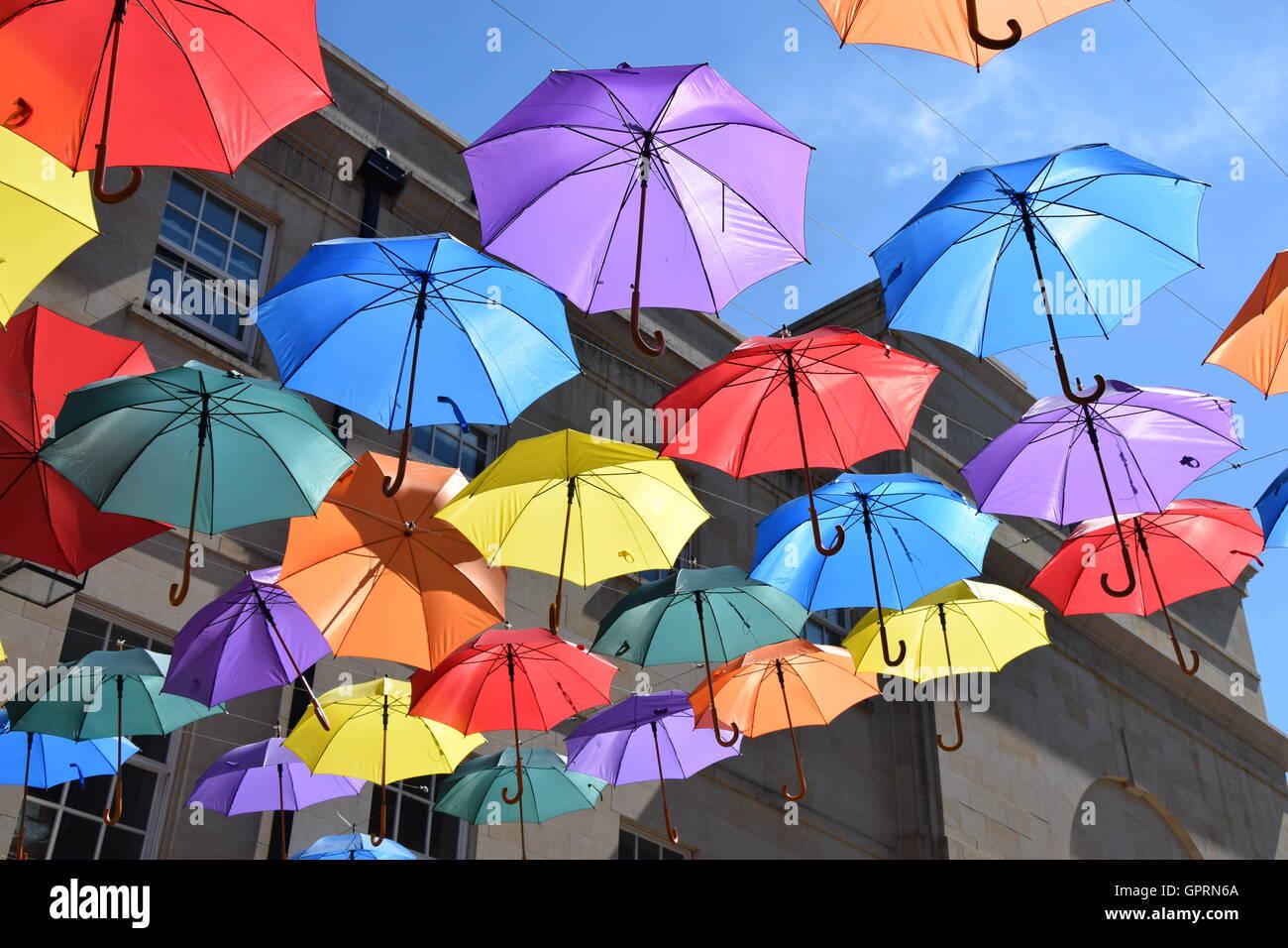 Bunte Schirme gegen blauen Himmel über einer Straße Stockbild