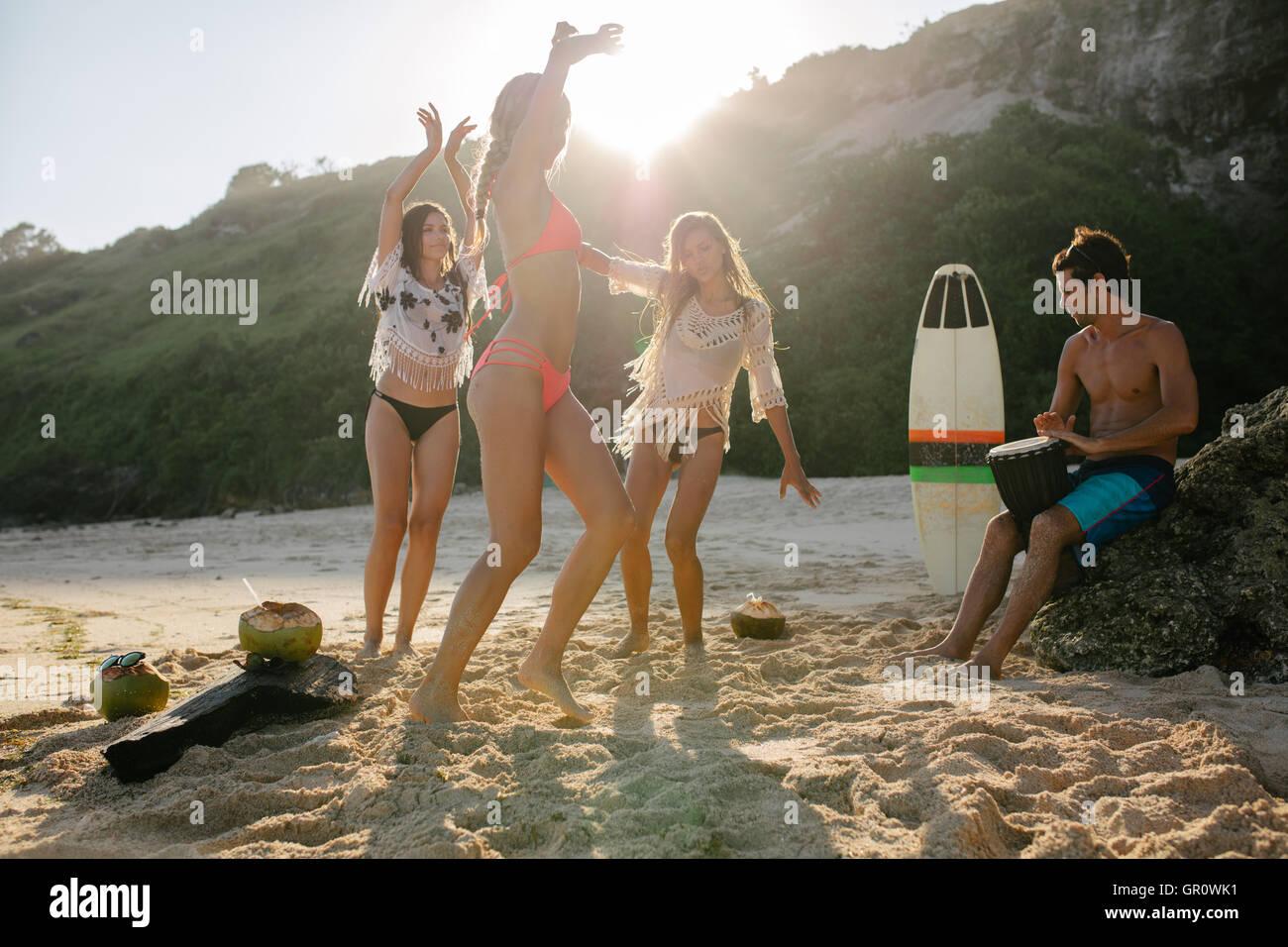 Gruppe junger Freunde am Strand feiern und tanzen. Junge Leute, die Spaß am Beach-Party, Frauen tanzen und Stockbild