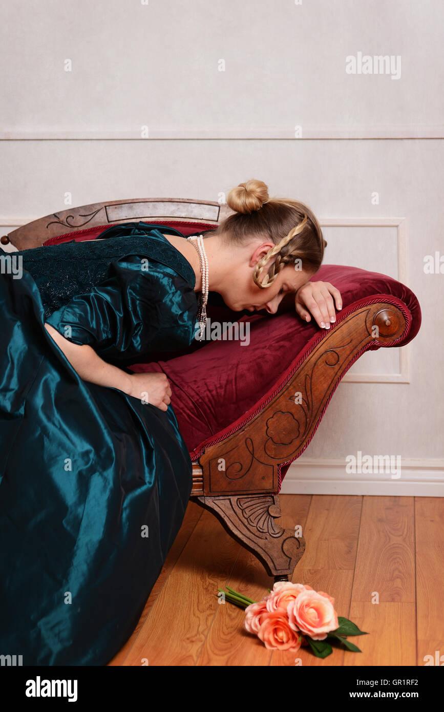 traurige viktorianische Frau auf Ohnmacht couch Stockbild