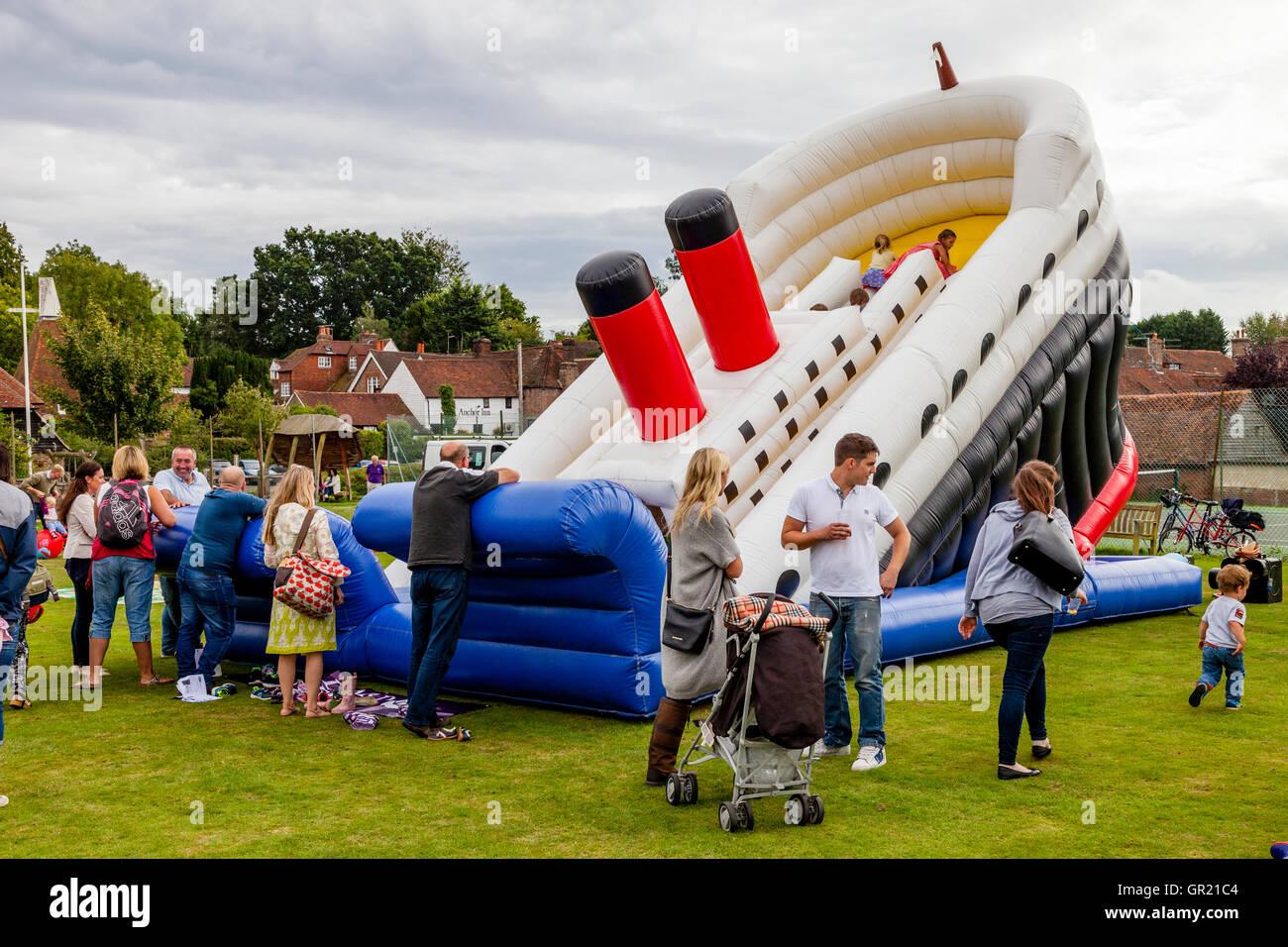 Kinder spielen auf einer Hüpfburg am jährlichen Hartfield Dorffest, Hartfield, East Sussex, UK Stockbild